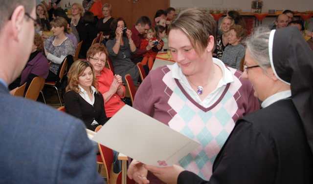 Stolz nehmen die 23 Absolventinnen des Montessori-Diplomkurses aus den Händen von Sr. Petra Stelzner und Detlef Burkhardt ihre Diplome entgegen. Foto: SMMP/Bock