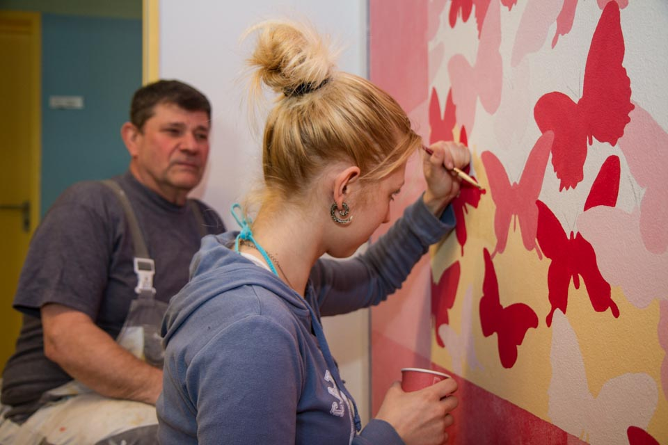Akribisch malt Steffi ihr Schmetterlingsmotiv an die Wand der Franenumkleide. Später möchte sie Maskenbildnerin werden. Foto: SMMP/Bock