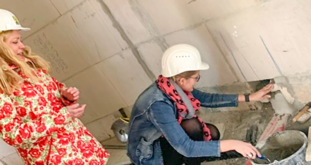 Symbolischer Akt: Heimleiterin Gisela Gerlach-Wiegmann und ihre Nachfolgerin Linda Agiri setzen die Zeitkapsel mit den Dokumenten der Grundsteinlegung in eine Wand des Neubaus ein. Foto: SMMP/Michael Lüdtke