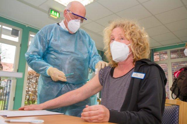 """Dr. Hermann Schlummer impft die Betreuungskraft Eva Harting. Ihr Mann arbeitet auf einer Intensivstation: """"Für uns war schnell klar, dass wir die Impfung wollen."""" Foto: SMMP/Ulrich Bock"""