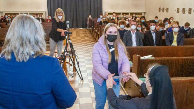 Schulleiterin Gaby Petry übergibt den Vertreterinnen und Vertretern aus den einzelnen Klassen die 50 Euro Startkapital für ihre Spendenaktionen. Foto: SMMP/Ulrich Bock